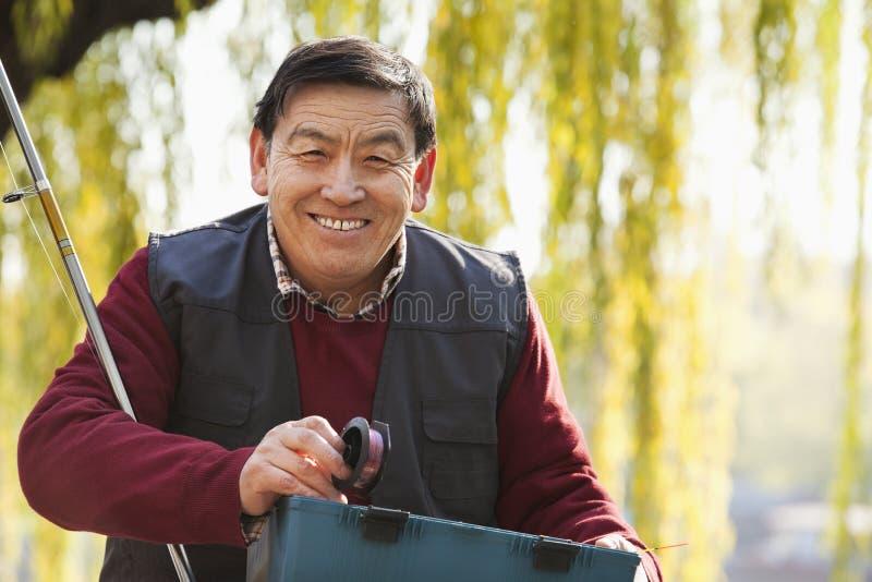 Senior portrait with fishing tackle box stock image