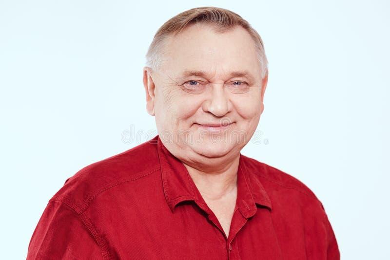 Senior portrait. Portrait of smiling aged man wearing red shirt against white background - retirement concept stock image