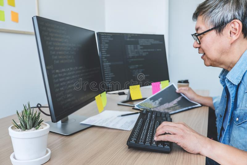 Senior Professional programmer working at developing programming and website working in a software develop company office, writing stock photography