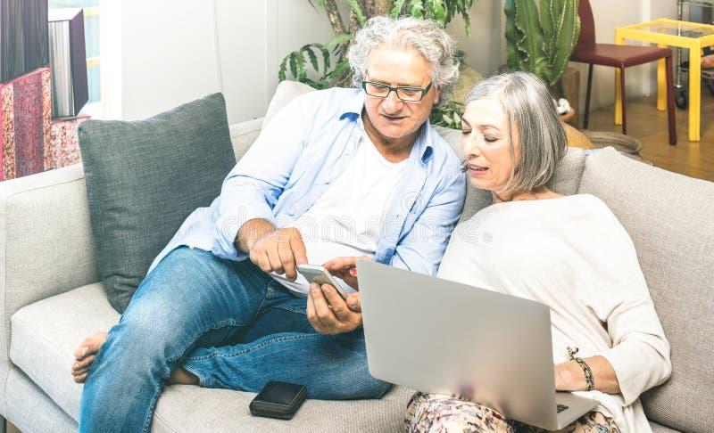Senior przechodzić na emeryturę para używa laptop na kanapie w domu przy online zakupy - starsze osoby i technologii pojęcie z do fotografia stock