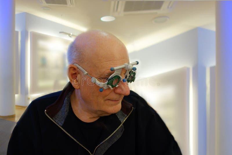 Senior przy okulistą bada nowych obiektywy w ślad ramie zdjęcie royalty free