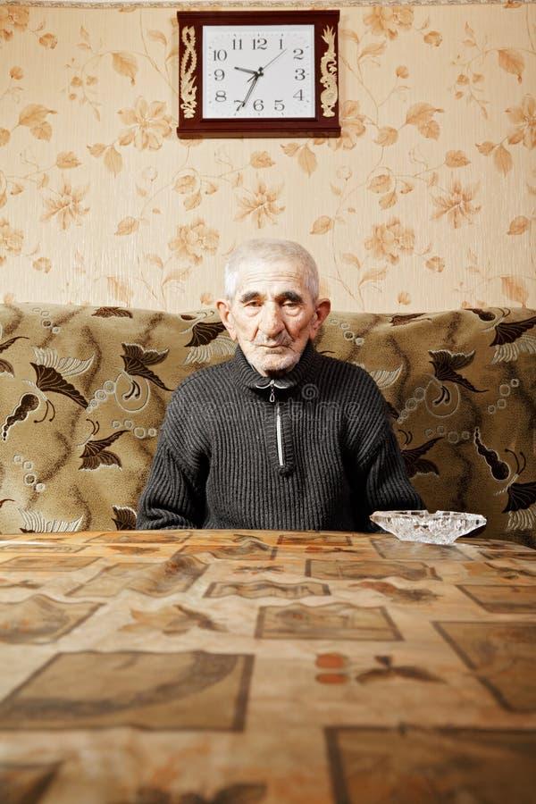 Senior przy stołem pod zegarem zdjęcia stock