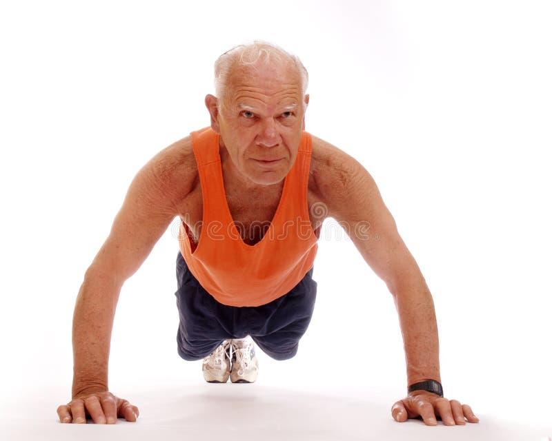 Senior Push-ups. Fit senior man doing push-ups. Isolated on white stock photo