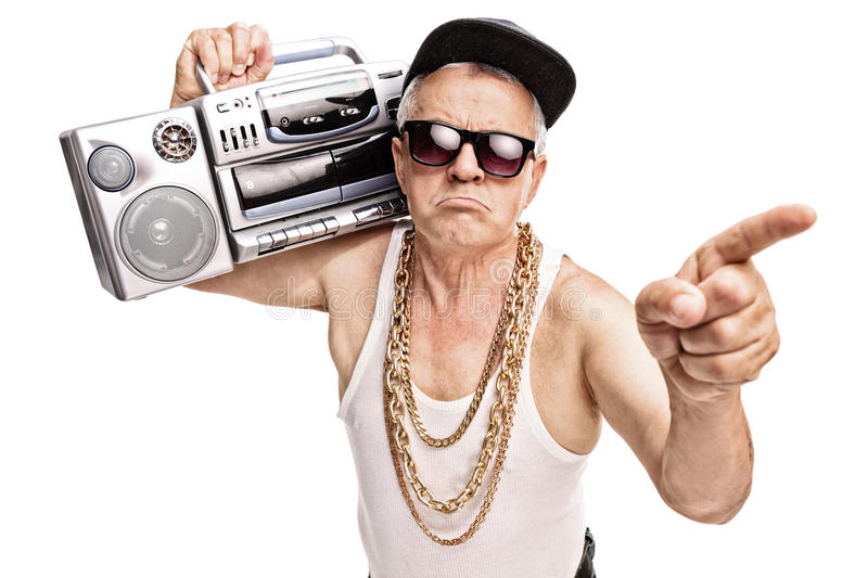 Senior rapper carrying a ghetto blaster on his shoulder. Grumpy senior rapper carrying a ghetto blaster on his shoulder and pointing with his finger isolated on stock image