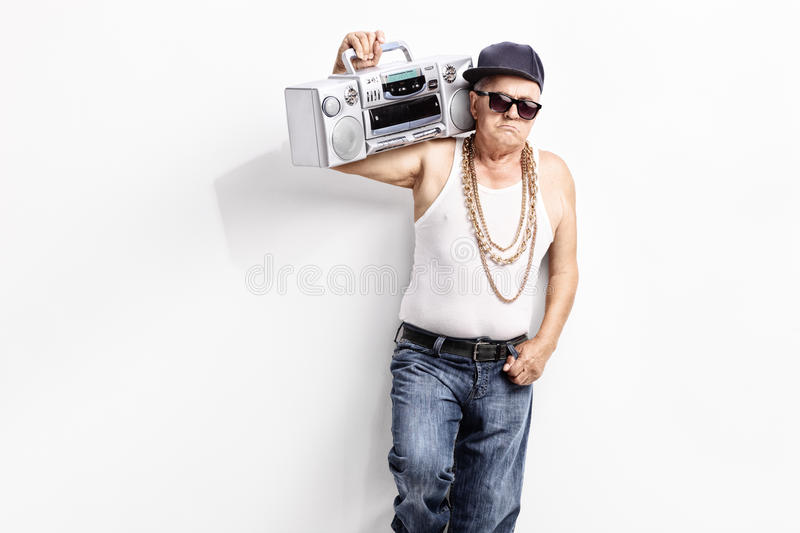 Senior rapper carrying a ghetto blaster. Senior man in a hip-hop outfit carrying ghetto blaster over his shoulder and looking at the camera royalty free stock image