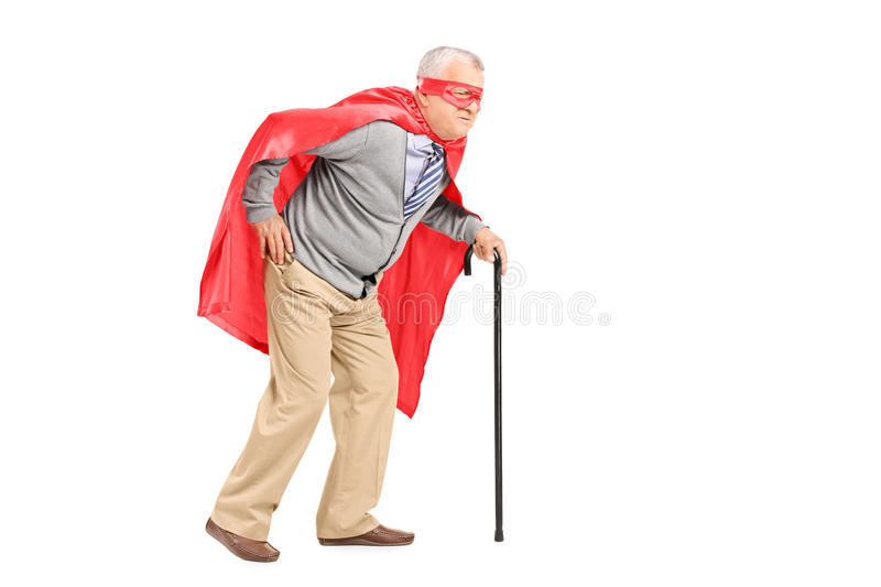 Senior with red cape and mask walking with cane. Isolated on white background stock photography