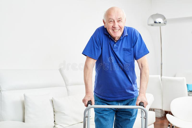 Senior in rehab learns walking with walker. And smiles optimistically royalty free stock photo