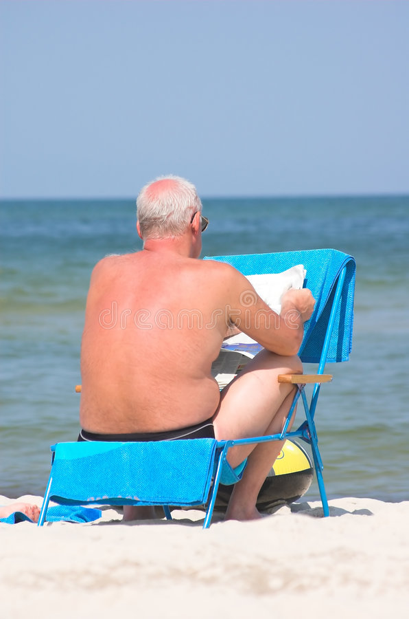 Senior relaxing by reading newspaper stock photography
