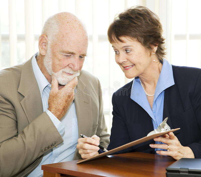Senior Reluctant To Sign Contract Stock Photos