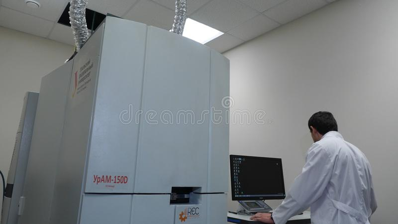 Senior researche rusing a computer in the lab while working on an experiment royalty free stock image