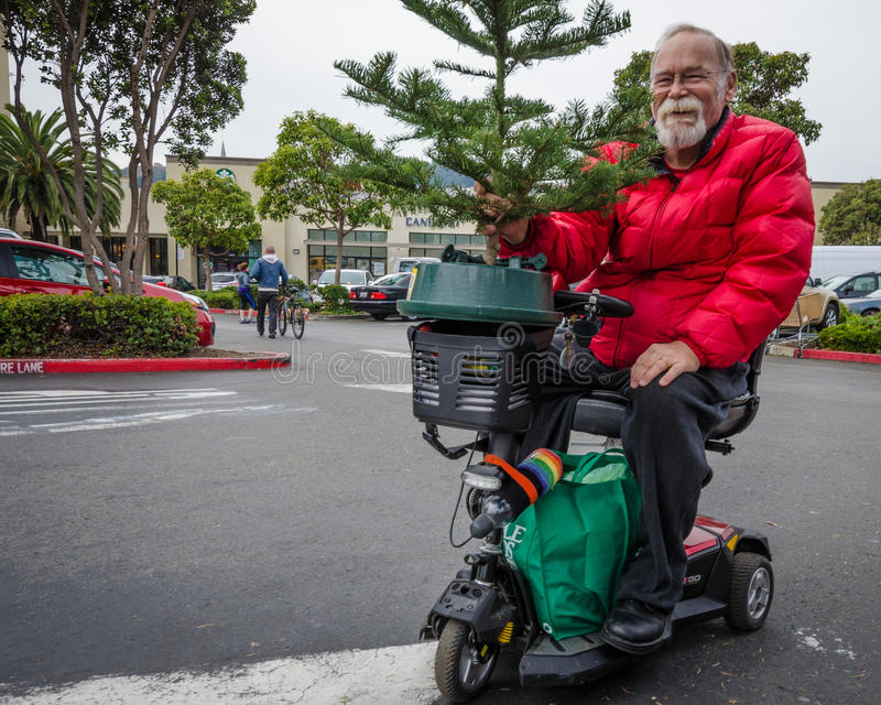 Senior resident of the Castro District is taking home a Christmas tree royalty free stock photo