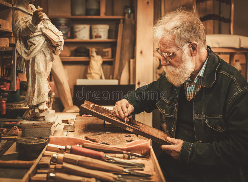 Senior restorer working with antique decor element in his workshop royalty free stock photo