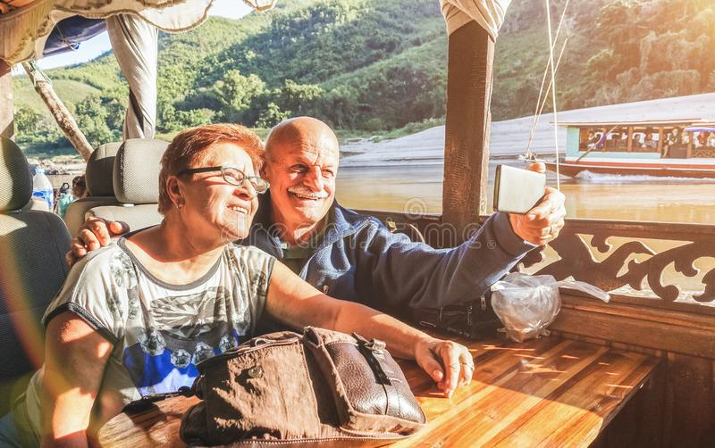 Senior retired couple of happy vacationers taking selfie at Mekong exploration tour with slowboat in Laos PDR - Active elderly stock photography