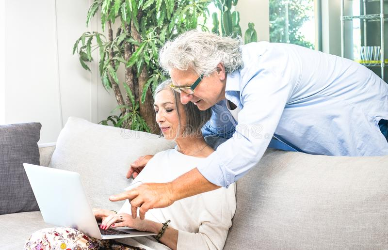 Senior retired couple using laptop computer at home on sofa - Elderly and technology concept with mature people watching shop stock image