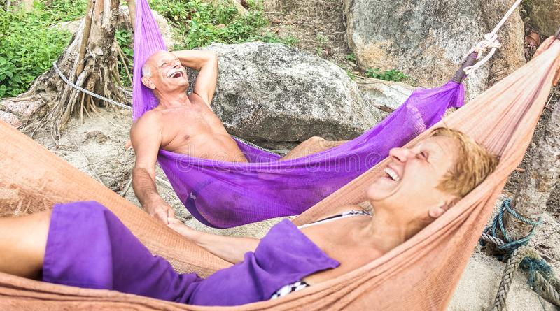 Senior retired couple vacationer relaxing on hammock at beach - Active youthful elderly and happy travel concept on tour around royalty free stock image