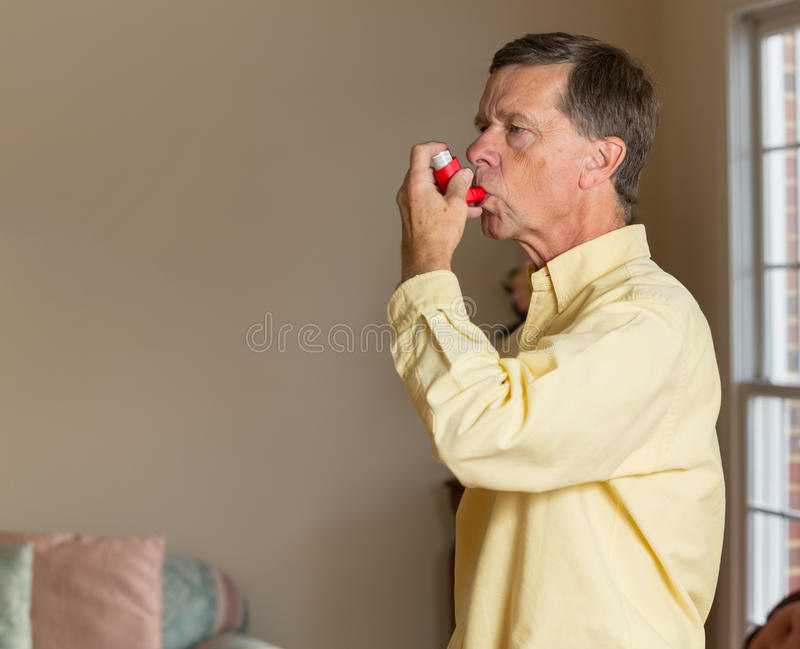 Senior retired man with asthma inhaler. Senior caucasian man at home with asthma inhaler to handle problems with breathing stock photography