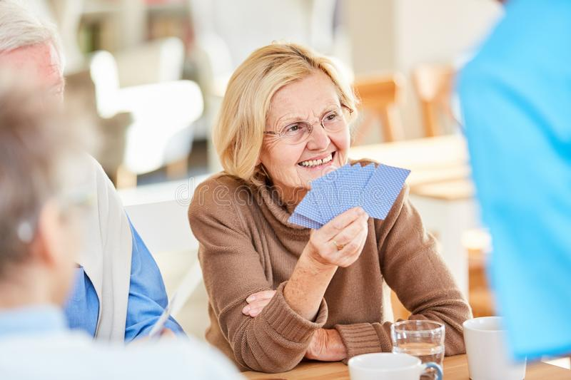 Senior retired woman is playing cards royalty free stock images