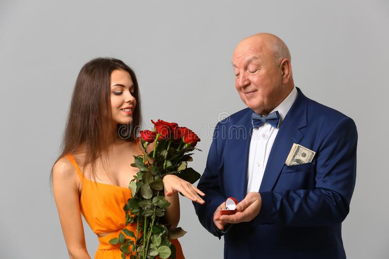 Senior rich man proposing to young woman on grey background. Marriage of convenience. Senior rich men proposing to young women on grey background. Marriage of stock photo