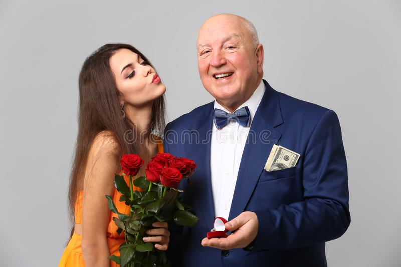 Senior rich man proposing to young woman on grey background. Marriage of convenience. Senior rich men proposing to young women on grey background. Marriage of stock image