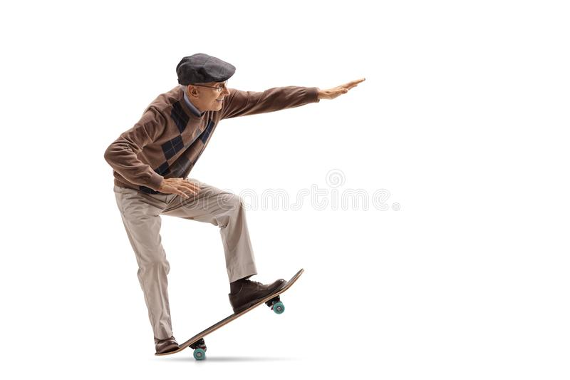 Senior riding a skateboard and doing a manual. Full length profile shot of a senior riding a skateboard and doing a manual isolated on white background stock photo
