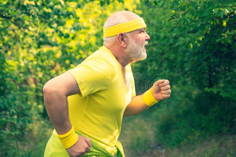 Senior runner in nature. Cardio workout. Running in park in the morning. Senior male is enjoying sporty lifestyle stock photo