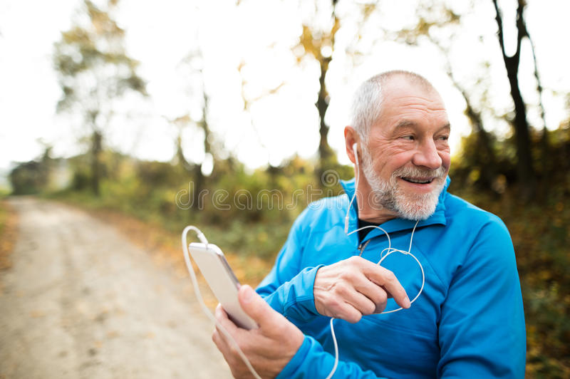Senior runner in nature with smart phone with earphones. royalty free stock photo