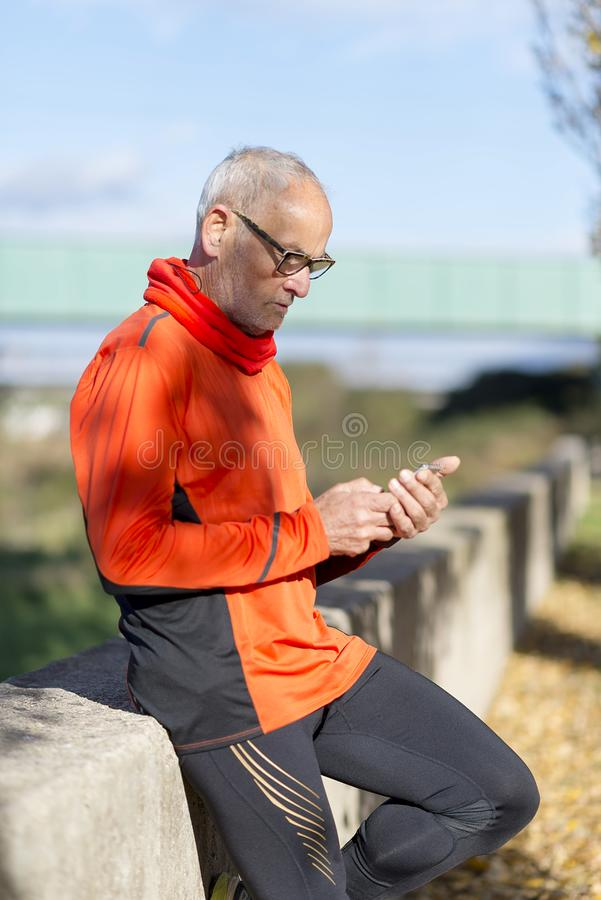 Senior runner man watching his smartphone after jogging royalty free stock image