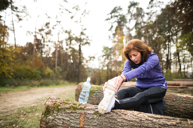 Senior runner sitting on wooden logs, stretching, drinking water stock image