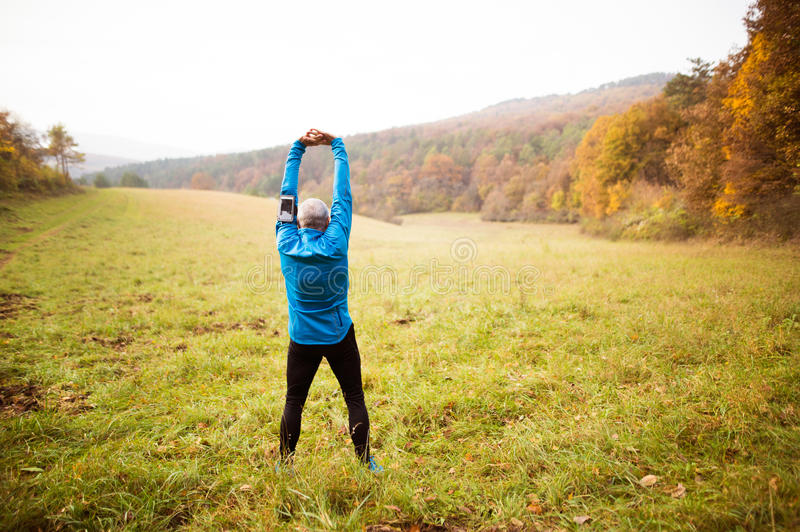Senior runner with smartphone doing stretching. Autumn nature. stock photos