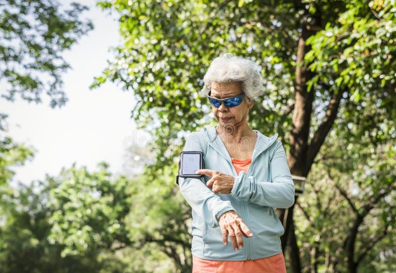 Senior runner using a fitness tracker royalty free stock image