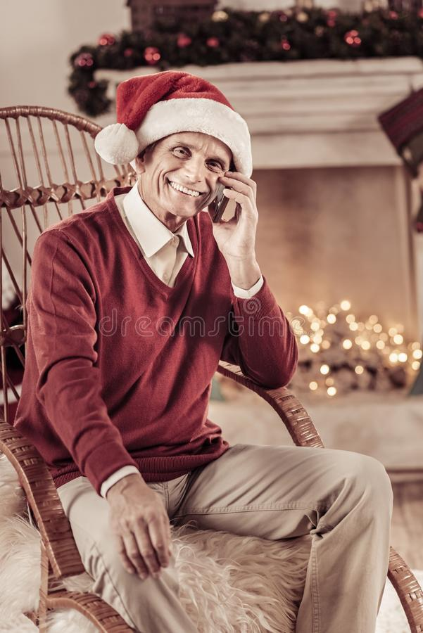 Senior satisfied man smiling and communicating. Ready for holyday. Senior satisfied funny man in a red hat sitting near the fireplace smiling and communicating stock photography