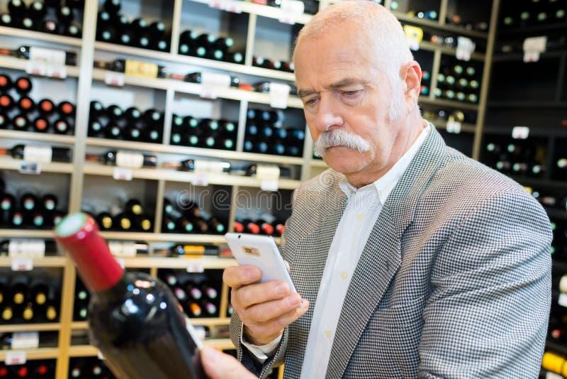Senior scanning barcode on wine bottle through smartphone royalty free stock photography