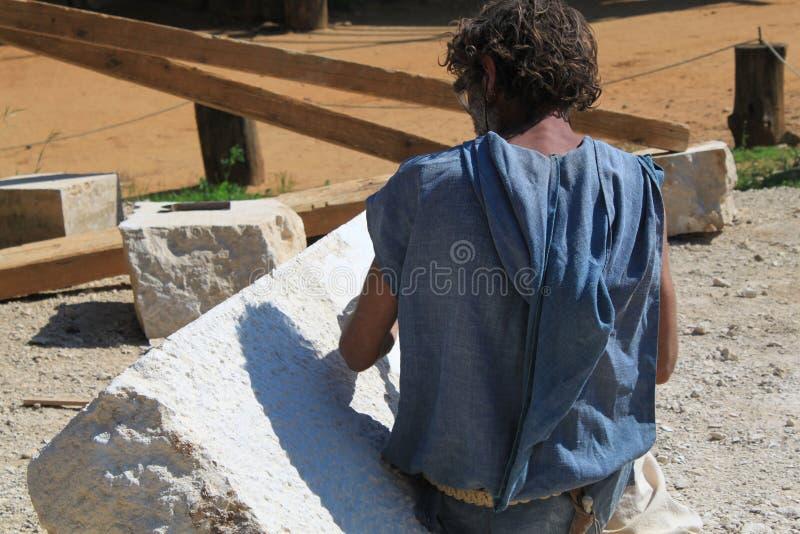 Senior sculptor werkt met stenen sculptuur stock fotografie