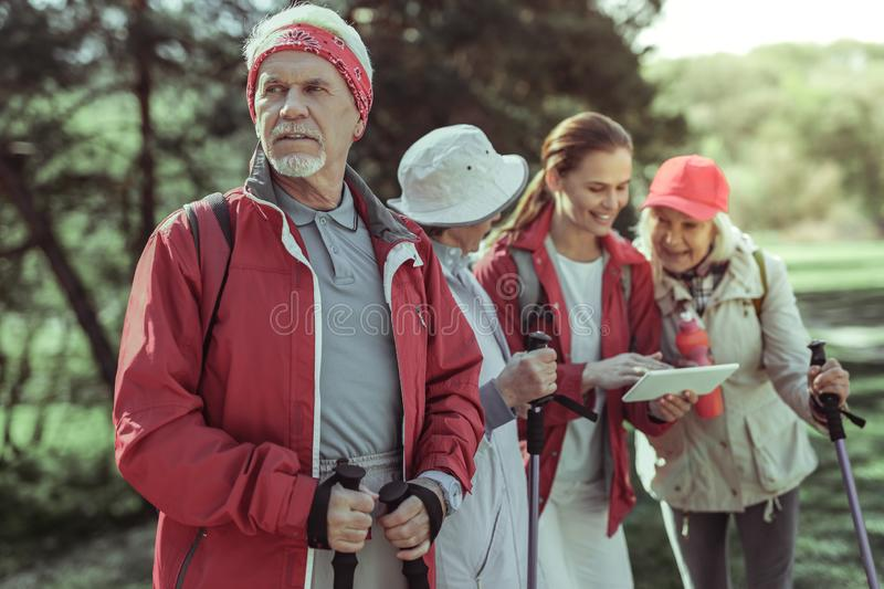 Senior serves as a guide for a group of amateur tourists royalty free stock images