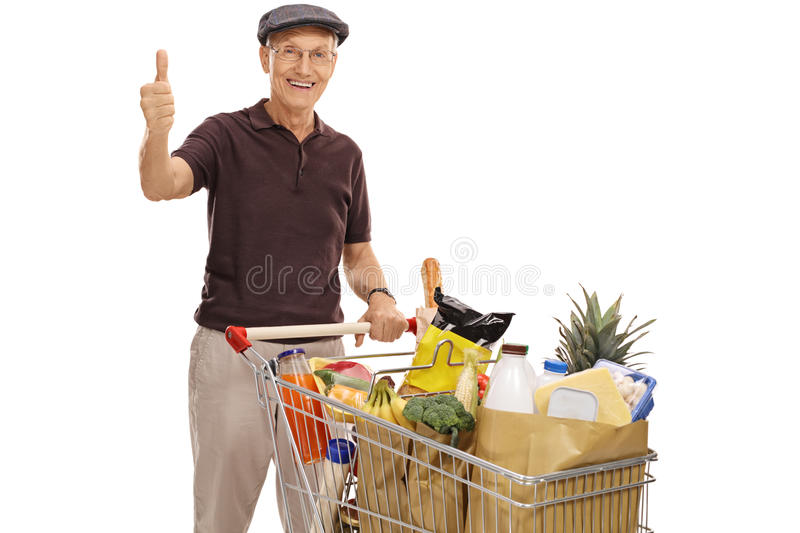 Senior with a shopping cart and giving a thumb up. Cheerful senior posing with a shopping cart full of groceries and giving a thumb up isolated on white royalty free stock image