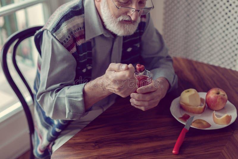 Senior siedzi samotnie w kuchennym łasowania śniadaniu z popielatym włosy i broda zdjęcie stock