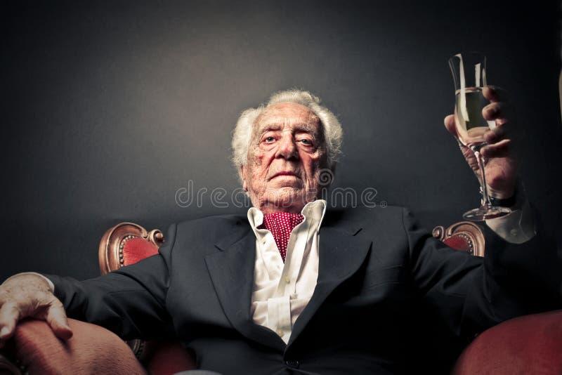 Senior sitting on armchair stock images