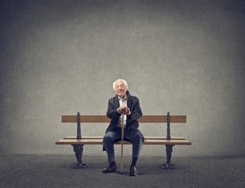Senior sitting on a bench stock photo