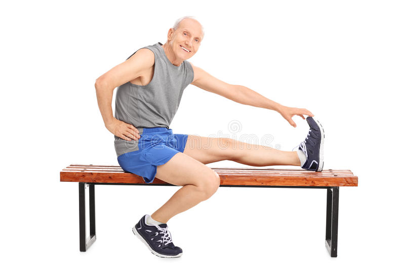 Senior sitting on a bench and stretching his leg stock photo