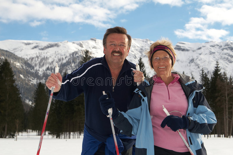 Senior skiing. A senior couple outdoor in a winter setting. The active couple is about to go crosscountry skiing royalty free stock photo