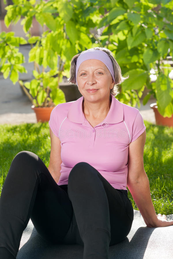 Download Senior Sportive Woman Sitting On Mat Sunny Stock Photo - Image: 21941276