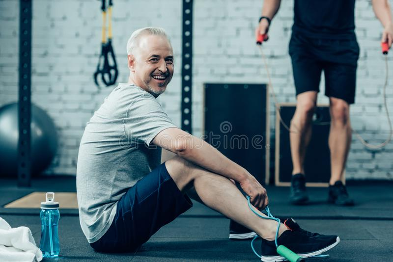 Senior sportsman resting while young sportsman training with skipping rope. In gym royalty free stock photo