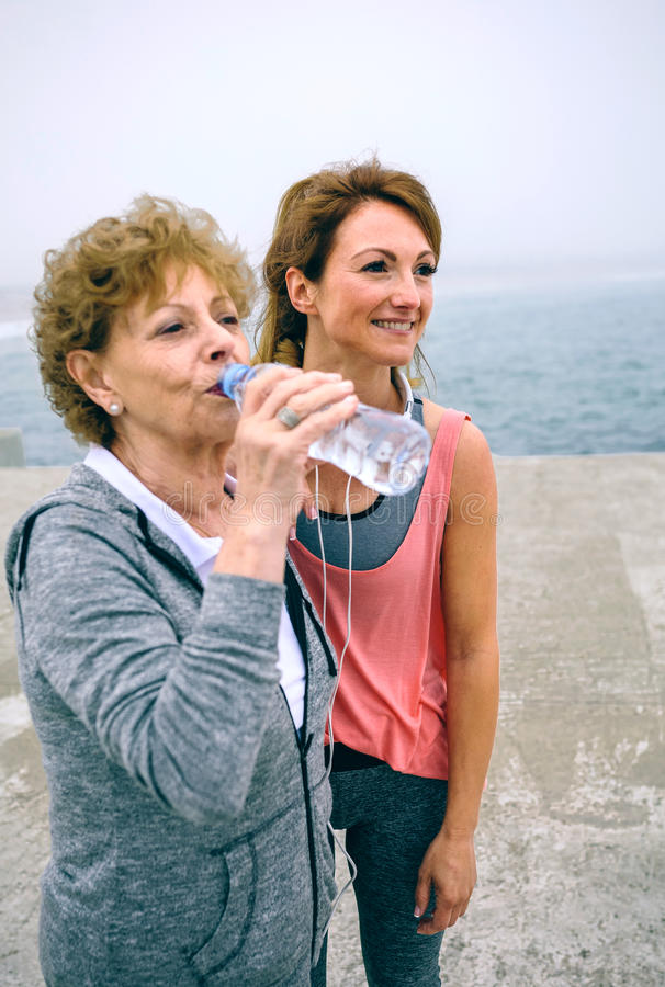 Senior sportswoman drinking water with female coach stock image