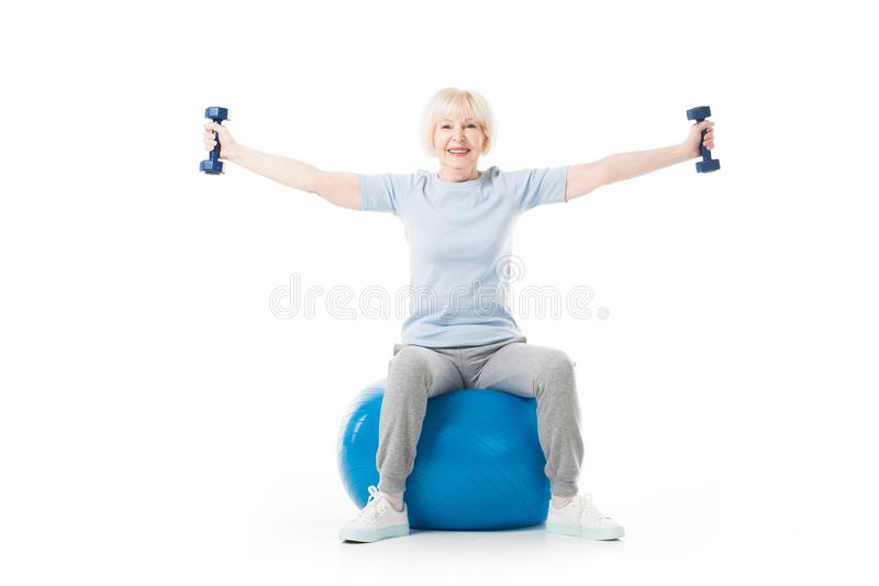 Senior sportswoman with dumbbells in wide hands sitting on fitness ball. Isolated on white royalty free stock photography