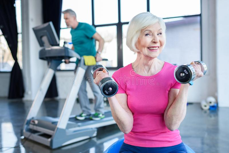 senior sportswoman sitting on fitness ball with dumbbells sportsman on treadmill behind in senior fitness class stock photo