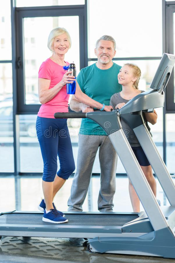 senior sportswoman sitting on fitness ball with dumbbells sportsman on treadmill behind in senior fitness class royalty free stock photo