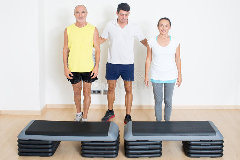 Senior step exercise with personal trainer stock photography