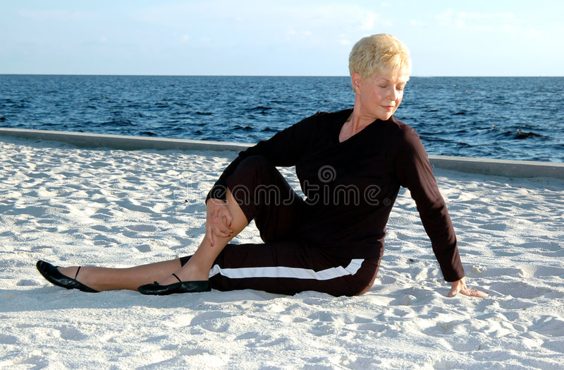 Senior stretching. A senior woman stretching on the beach stock photo
