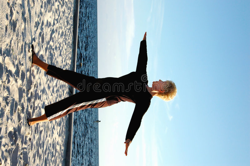 Senior stretching. A senior woman stretching on the beach royalty free stock photography