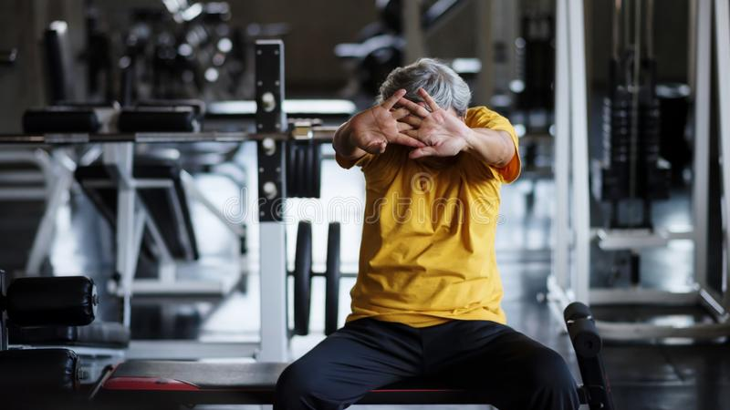 Senior strong man stretch hands in gym royalty free stock photo